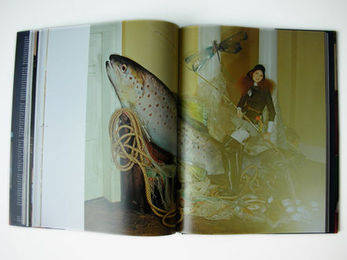 Lily Cole in traditional fishing gear riding a giant fish in a formal country house room.