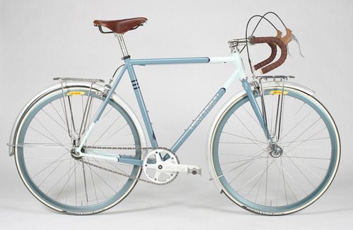 Single speed bike blue rims white tires and chrome luggage racks, leather-bound handle bar and saddle